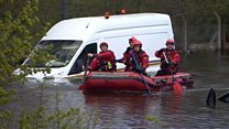 Emergency services check flooded vehicles