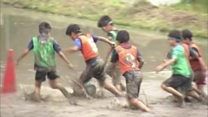 Children play football in a rice paddy