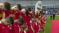 Cliftonville players bow heads during anthem