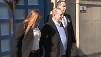 Harvey Weinstein smiles in handcuffs