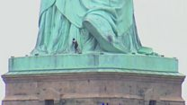 Person climbs to Statue of Liberty base