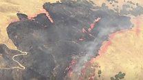 Brush fire burns in Californian hills