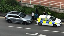 Moment armed police detain two men