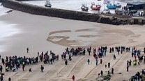 Timelapse: Wilfred Owen's face drawn in sand