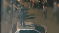 Footage shows football fan jumping on car