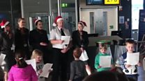 Children pass the time at Gatwick with carols