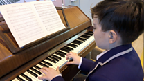 Refugee, 11, plays piano at charity shop