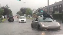 Man sits on top of flooded car