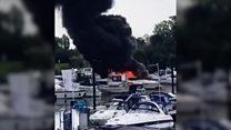 Black smoke billows from marina boat fire