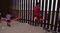 Children play on seesaws at US-Mexico border