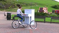 Singer cycles with piano on her bike