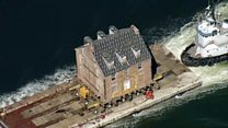 Aerials of historic home being moved by boat