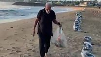 India's Narendra Modi picks litter on beach