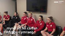 Mae tîm merched Cymru'n dysgu Cymraeg