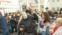 Women try to rip masks off men detaining protesters