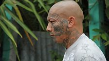 A Mara Salvatrucha member shows his facial tattoos