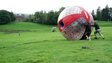 """Greg and Producer Sarah """"Sphere Rolling"""" down the hill outside the country house"""