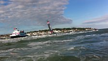 Sir Ben Ainslie passes the finish line on his AC45
