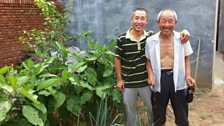 Mr Bai with his father outside their home