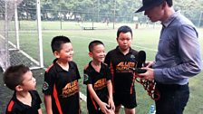 Children playing football at the China Club Football FC Summer Camp in Beijing