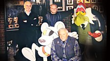 Brian Cosgrove, David Jason and Mark Hall (kneeling) with cut-outs of Danger Mouse and Count Duckula's butler Egor in 2001