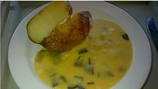 Jacket potato with leeks in a cheese sauce.