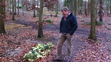 Tom looking at a recent grave at the Sustainability Centre, marked with fresh flowers.