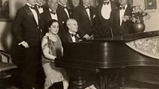 Ravel at the piano, during his American tour. At far right is George Gershwin.