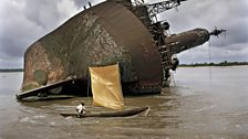 A fisherman passes the wreck of an old ship off Greenville. Liberia is scattered with wrecks owing to the 14 year civil war.
