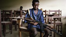 Sekou, 12, an LURD rebel, in an abandoned Tubmanberg classroom. His parents died in the war. He joined the group to survive.