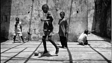Street kids play in a derelict Monrovia builing. Despite the social breakdown, football still brings youths together.