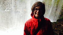 Felicity standing behind the waterfall at Sgwd yr Eira, in Brecon Beacons Waterfall Country