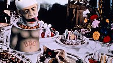 Terry Gilliam artwork of half a man with a bandaged head on a banquet table surrounded by food.