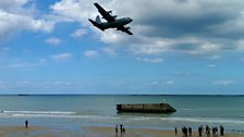 A plane flies over the beach at Arromanches