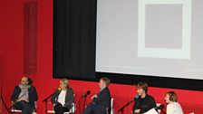 Free Thinking panel discussing abstract art beneath a projection of Malevich'sBlack Square 1929
