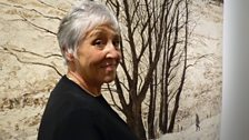 Artist Victoria Crowe next to the tapestry of her painting Large Tree Group