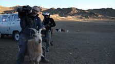 Producer/director Alexis Girardet pretends to ride a friendly goat with soundman Mark Roberts in the background
