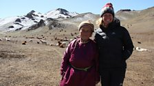 Kate and 78 year old matriarch, Chimed, stand in the snow capped mountains of the Gobi Desert