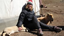 Kate sits with George the puppy and Zegle the goat outside the nomads Ger
