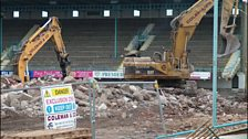 The West Stand is obscured by machinery.