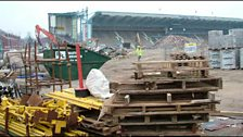 The view of the Main Stand is obscured by building supplies.