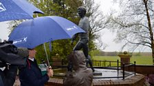 Norma Morton and presenter Alex are discussing Jim's love of the rain next to his statue in Hill O'Beath