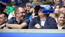 Leicester City fans share a laugh in the stands