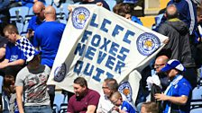 Leicester City fans in the stands hold up a banner
