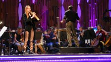 Jess Gillam rehearses on stage at the Barbican Centre with the BBC Symphony Orchestra and Mark Wigglesworth