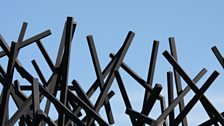 A seemingly chaotic dome of black rods is positioned over a grass plinth – a reference to Chaos Theory.