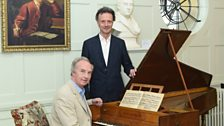 Duke of Buccleuch at Handel's harpsichord, with curator Paul Boucher at Boughton House.