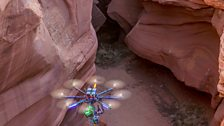 Piloting a large, remotely operated drone through the narrow walls of a slot canyon.