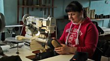 Olga Kuznetsova sews the labels and piping onto the slipper boots