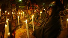 At a cemetary in Oaxaca, villagers light candles
